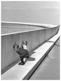 Two kids peering through a hole in a wall